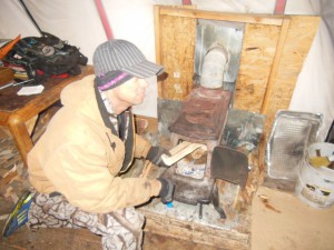Angelo putting wood into stove to warm tent