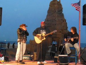 Nick Clemons with Adam Bro and Jim Keegan in a moving musical tribute by the sandcastle in a setting sun